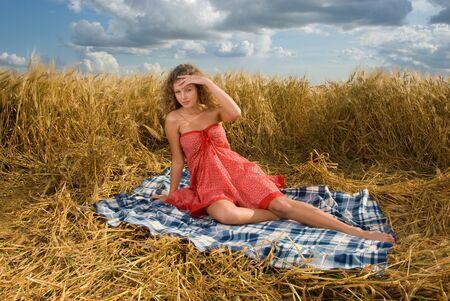 Beautiful slavonic girl on picnic in wheat field photo