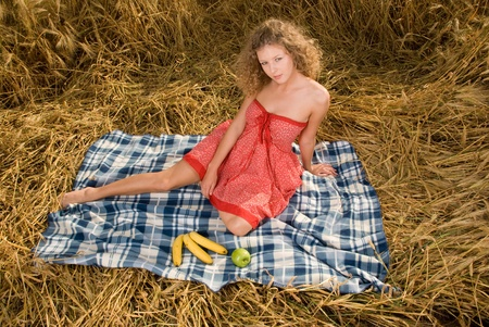 Beautiful slavonic girl on picnic in wheat field with apple and banana photo