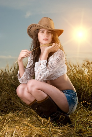 Beautiful slavonic girl in cowboy clothes pose in wheat field photo