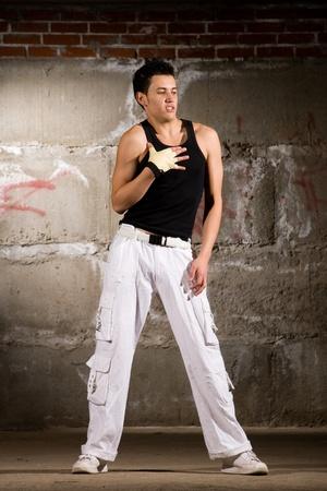 Hip hop men dancing in modern style over grey brick wall Stock Photo - 8396884