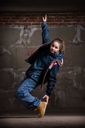 Hip hop girl dancing in modern style over urban grey brick wall photo