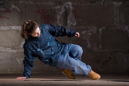 Hip hop girl dancing in modern style over urban grey brick wall photo