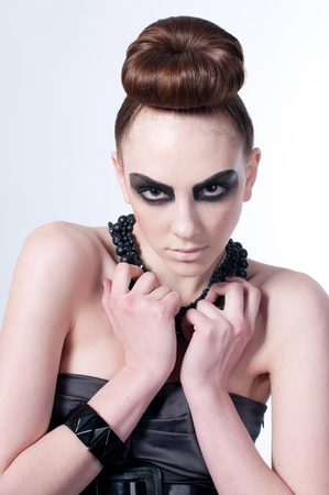 Studio shot of a young, beautiful, fashion model with black make-up, dress and beads Stock Photo - 8497549
