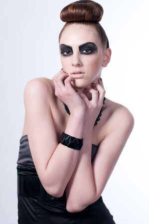 Studio shot of a young, beautiful, fashion model with black make-up, dress and beads Stock Photo - 8497154
