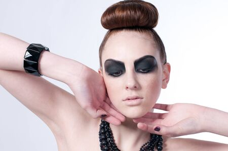 Studio shot of a young, beautiful, fashion model with black make-up, dress and beads Stock Photo - 8497164