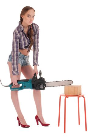 Young playful woman in jeans coverall and shirt holding huge chain saw photo