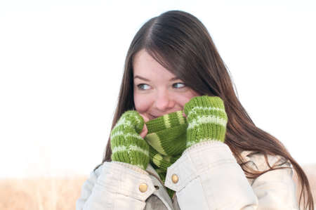 Winter lifestyle. Beautiful girl with green scarf and gloves over snow landscape Stock Photo - 8512852