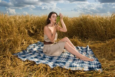 Beautiful slavonic girl on picnic in wheat field with grapes photo