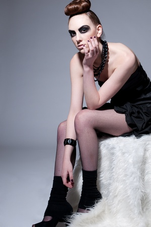 Studio shot of a young, beautiful, fashion model with black make-up, dress and beads photo