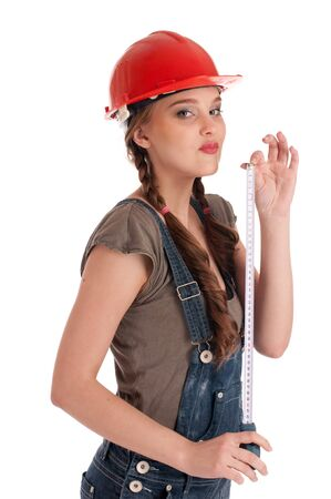Young playful woman in jeans coverall and orange helmet holding tape measure Stock Photo - 8528717