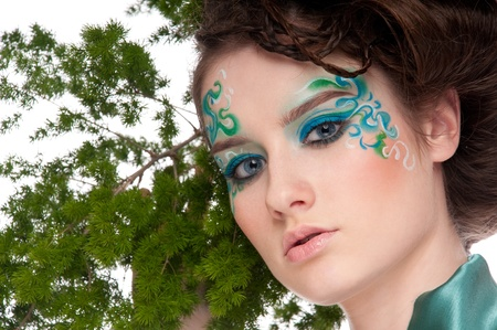 Close-up portrait of beautiful  girl with green face art on white posing with plant photo