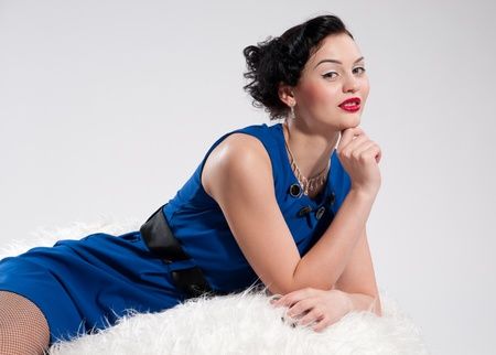 Beautiful glamour woman in blue dress on white fur sofa Stock Photo - 8528769