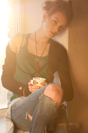 Beautiful young woman in casual wear dreaming with cup of hot coffee over window. Sun beam. photo