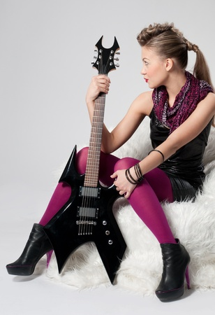Beautiful young rock girl in purple stocking with black electric guitar sitting on white fur sofa photo