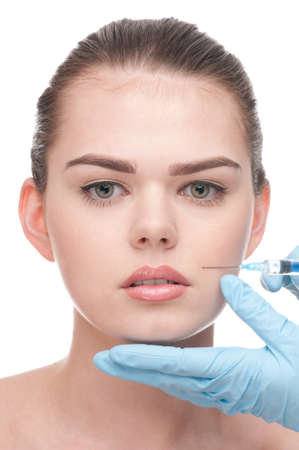 cosmetic injection of botox to the face of beautiful woman - close-up portrait isolated on white photo