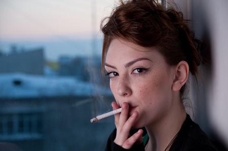 Beautiful young woman in casual wear smoking on window. Over evening  city. photo