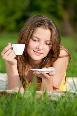 Beautiful young woman drink hot tee outdoor on green grass photo