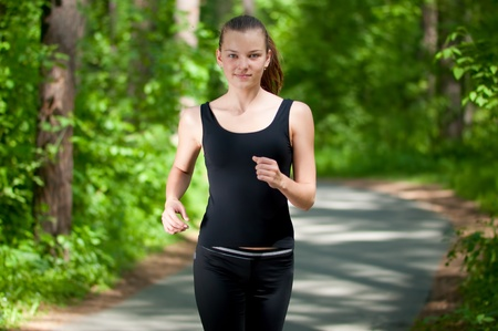 Beautiful young woman running in green park on sunny summer day Stock Photo - 8571885