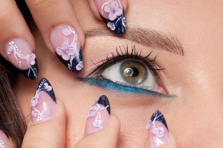 Closeup eyes make-up zone. Nail art. Finger.  Pink and blue color. High resolution.  photo
