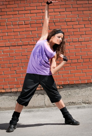 Beautiful teenage girl dancing hip-hop over red brick wall Stock Photo - 8571563