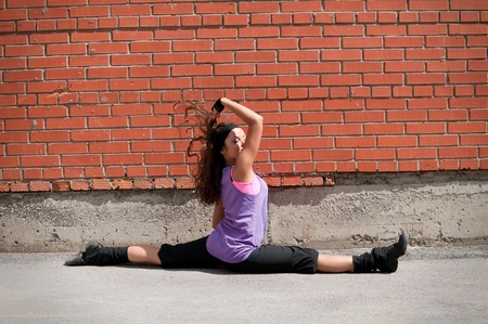 Beautiful teenage girl dancing hip-hop over red brick wall Stock Photo - 8570725
