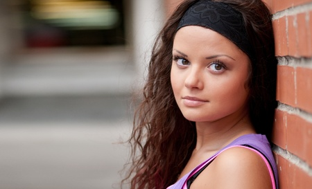 Beautiful teenage girl pose over red brick wall Stock Photo - 8571653