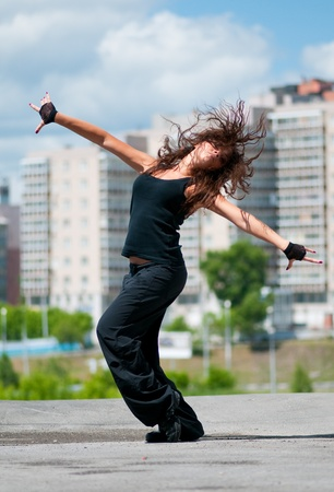 Beautiful teenage girl dancing hip-hop over urban city landscape
