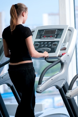 Young woman at the gym exercising. Run on on a machine. Stock Photo - 8571942