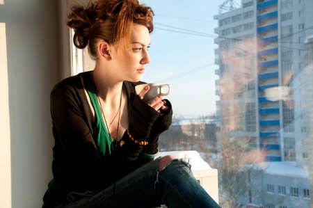 Beautiful young woman in casual wear dreaming with cup of hot coffee over window Stock Photo - 8593803