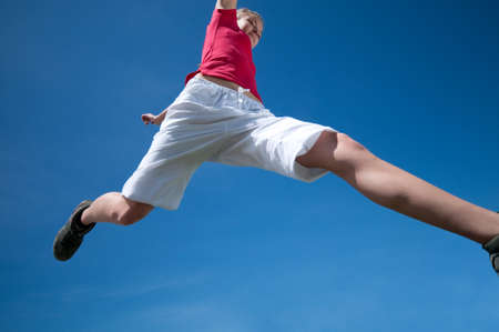 Beautiful young woman jump into blue sky on sunny summer day photo