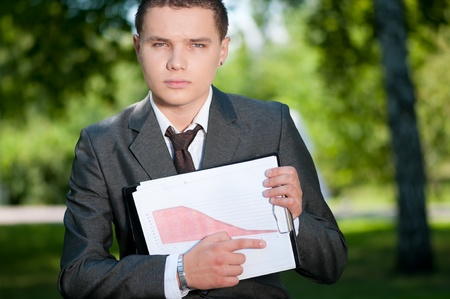 Young business man show graph on outdoor meeting, at green park. Student. Stock Photo - 8605829