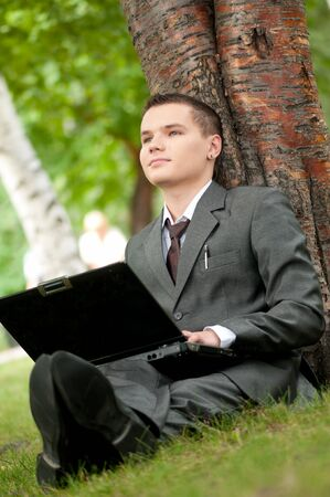 Young business man working on notebook laptop computer, at green park. Student. photo