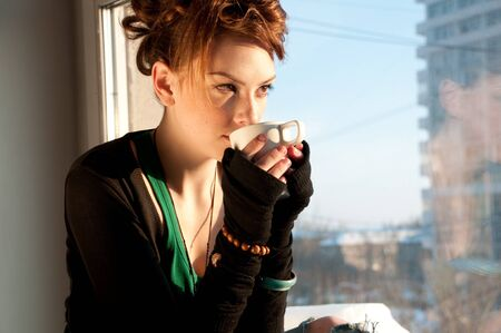 Beautiful young woman in casual wear dreaming with cup of hot coffee over window Stock Photo