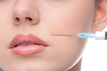 cosmetic injection of botox to the face of beautiful woman - close-up portrait isolated on white