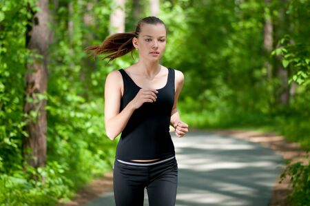Beautiful young woman running in green park on sunny summer day Stock Photo - 8640379