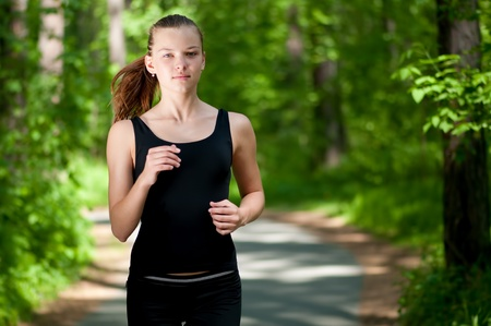 clean street: Beautiful young woman running in green park on sunny summer day Stock Photo