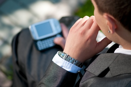 Young business man talking by mobile cell phone, at green park. Student. photo