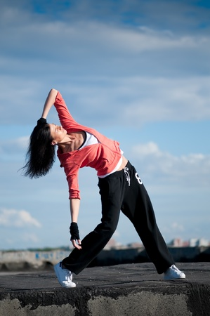 Beautiful woman dancing hip-hop modern style over urban city landscape and blue sky photo