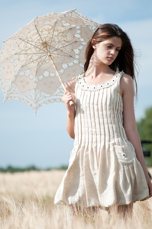Beautiful sad and lonely woman with umbrella walking in wheat field. Timed. Stock Photo - 8640143