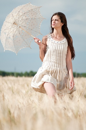 Beautiful sad and lonely woman with umbrella walking in wheat field. Timed. Stock Photo - 8640087