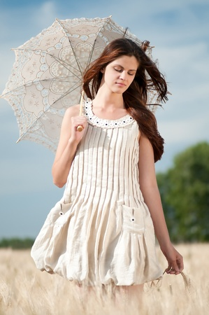 farm girl: Beautiful sad and lonely woman with umbrella walking in wheat field. Timed. Stock Photo