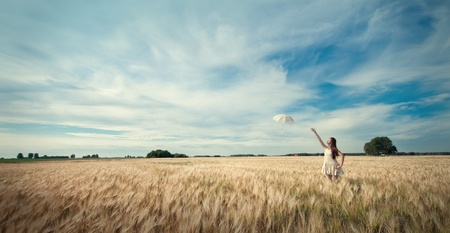 Beautiful sad and lonely woman with umbrella walking in wheat field. Timed. Stock Photo - 8640456