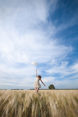 Beautiful sad and lonely woman with umbrella walking in wheat field. Timed. Stock Photo - 8640598
