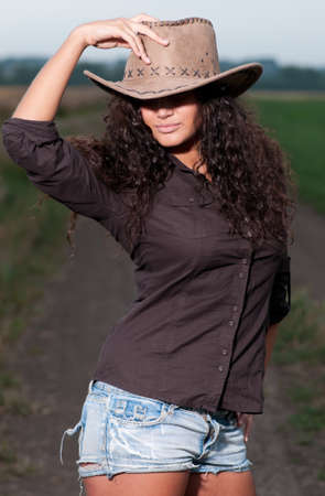 doğal olarak: Beautiful cowboy woman with perfect hair and skin posing in country field