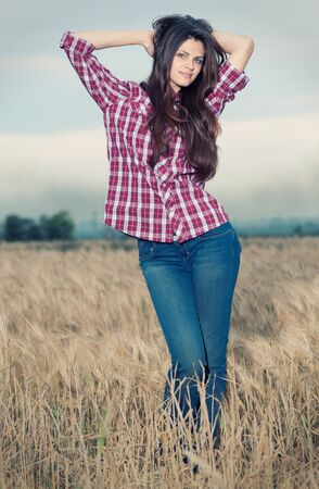 Beautiful cowboy woman with perfect hair and skin posing in country field Stock Photo - 8640610