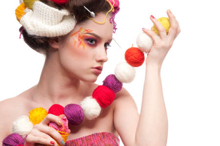 Closeup portrait of beautiful fashion woman with color face art. All in knitting style. Wool balls. Beads photo