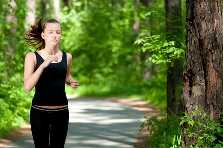Beautiful young woman running in green park on sunny summer day Stock Photo - 8708029