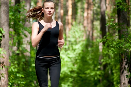 woman running: Beautiful young woman running in green park on sunny summer day Stock Photo
