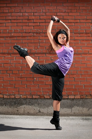 Beautiful teenage girl dancing hip-hop over red brick wall Stock Photo - 8715751