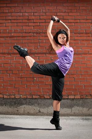 Beautiful teenage girl dancing hip-hop over red brick wall Stock Photo - 8715751